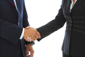 Mature Caucasion business male and female shaking hands