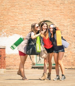 Group of happy best friends with shopping bags taking a selfie i
