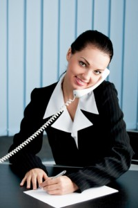 Businesswoman on phone signing document at office