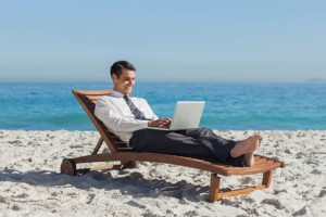 Young businessman lying on a deck chair with his laptop on the beach