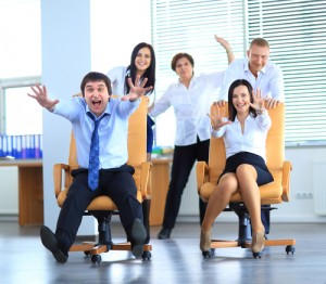 Happy office employees having fun at work in an office chair race