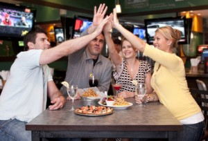 Group of friends having fun in a sport bar and raising hands, very cheerful.