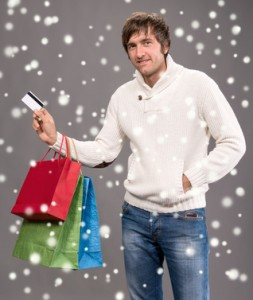 Handsome man holding shopping bags and credit card. Christmas and holidays concept