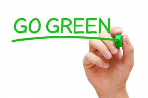 Hand writing Go Green with green marker on transparent wipe board.