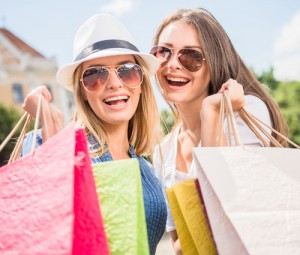 Portrait of attractive young women in sunglasses with shopping bags looking at camera and smiling.