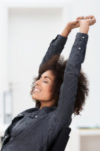 African American businesswoman relaxing at work reclining back in her chair stretching her arms in the air and closing her eyes in contentment