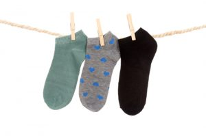 three socks hanging on a rope clothesline isolated on white